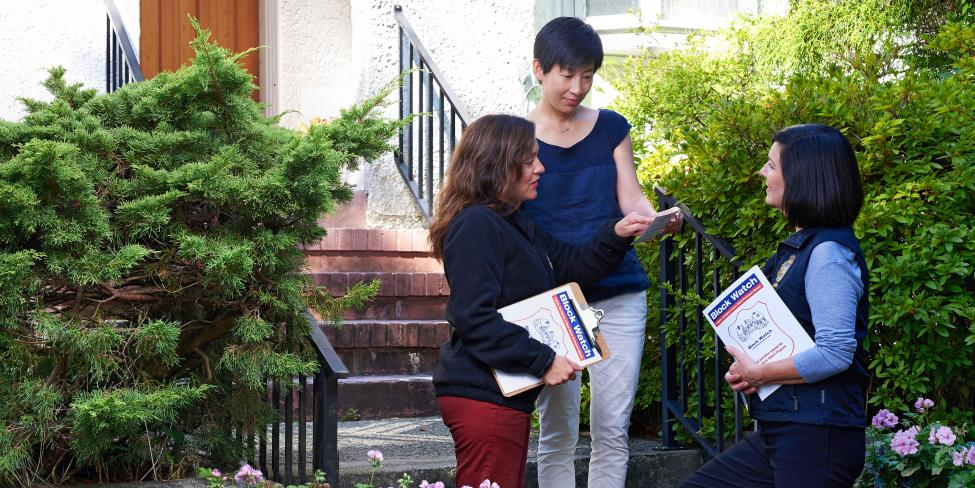 two Block Watch representatives (women) speaking with a homeowner (woman) about the block watch program