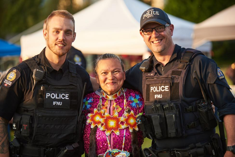 two uniformed officers standing next to a woman wearing First Nation regalia